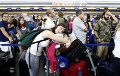 <p>Customers wait in line after a computer glitch crippled the baggage handling system at the American Airlines' Terminal 8 at New York's John F. Kennedy International Airport July 30, 2008. REUTERS/Joshua Lott</p>