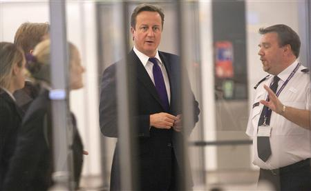 Britain's Prime Minister David Cameron watches passengers pass through immigration control during a visit to Terminal 5, at Heathrow Airport, west of London October 10, 2011. REUTERS/Richard Pohle/Pool