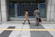 <p>A man looks at a stock quotation board outside a brokerage in Tokyo September 26, 2011.REUTERS/Toru Hanai</p>