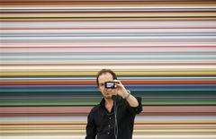 "<p>Paul Chaves, a visitor to the Frieze Art Fair, takes a picture of himself in front of Gerhard Richter's ""Strip"" in Regents Park, central London October 12, 2011. REUTERS/Andrew Winning</p>"