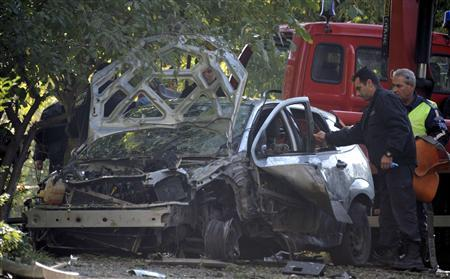 Bulgarian police inspect the damaged car of television journalist Sasho Dikov in Sofia October 14, 2011. REUTERS/Stringer