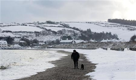 A man walks his dog on the beach near the village of Cushendun , in the Glens of Antrim, in Northern Ireland December 22, 2010.