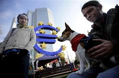 """<p>A protestor holds his dog """"Chucky"""" in a camp outside the headquarters of the European Central Bank (ECB) in Frankfurt October 18, 2011. REUTERS/Kai Pfaffenbach</p>"""