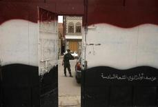 <p>A school door is painted with the colours of Yemen's national flag, as a soldier stands guard, on the first day of the General Secondary Examinations in Sanaa June 26, 2011. REUTERS/Suhaib Salem</p>