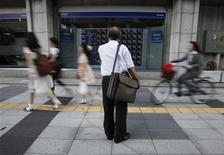 <p>A man looks at a stock quotation board outside a brokerage in Tokyo August 30, 2011. REUTERS/Toru Hanai</p>