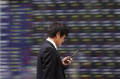 <p>A man walks past a stock quotation board outside a brokerage in Tokyo October 24, 2011. REUTERS/Toru Hanai</p>