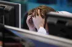 <p>A worker on IG Index's trading floor holds his head in his hands as markets tumble globally, in London September 22, 2011. REUTERS/Andrew Winning</p>