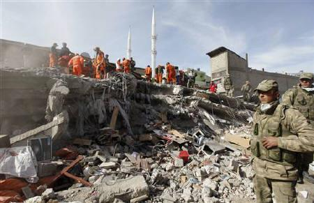 Soldiers stand near rescue workers working to save people trapped under debris after an earthquake in Ercis, near the eastern Turkish city of Van, October 24, 2011. REUTERS/Osman Orsal