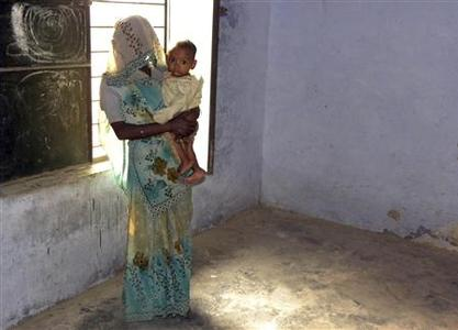 Phul Kumari, 25, stands with her child in front of a window in a village community centre in Baghpat district, located in India's northern state of Uttar Pradesh October 18, 2011. REUTERS/TrustLaw/Nita Bhalla