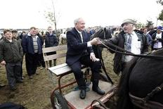 <p>Irish presidential candidate Martin McGuinness sits on a cart at the Ballinasloe Horse fair as he travels the country canvassing ahead of polling day in Ballinasloe, Ireland October 8, 2011. REUTERS/Cathal McNaughton</p>