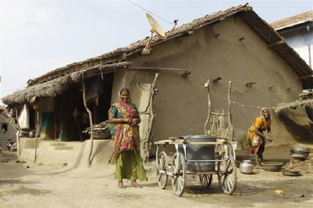 Villagers smile outside their mud house in Khun village near Dholera town in Gujarat October 12, 2011. REUTERS/Amit Dave