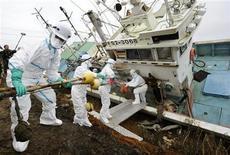 <p>Voluntarios del grupo Hiroshima City trabajan para remover material radiactivo de una embarcación pesquera en Minamisoma, en la prefectura de Fukushima.</p>
