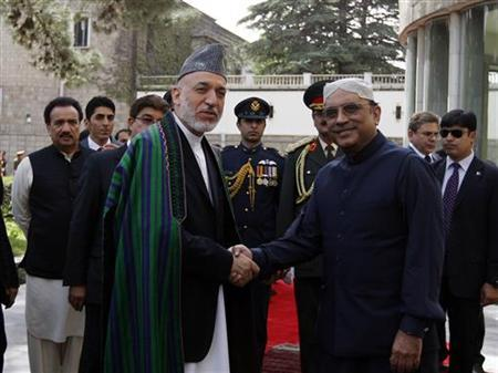 Afghanistan's President Hamid Karzai (L) shakes hands with his Pakistani counterpart Asif Ali Zardari in Kabul July 19, 2011. REUTERS/Omar Sobhani