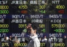 <p>A man is reflected on an electronic board displaying stock prices outside a brokerage in Tokyo October 31, 2011. REUTERS/Issei Kato</p>