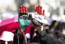 <p>An anti-government protester raises her hands, painted with the colours of the Yemen and Libyan national flags, during a sit-in calling for Saleh to be taken to the International Criminal Tribunal, in Sanaa November 2, 2011. REUTERS/Louafi larbi</p>
