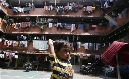 A child plays in front of an apartment complex in Jakarta October 21, 2011. REUTERS/Supri
