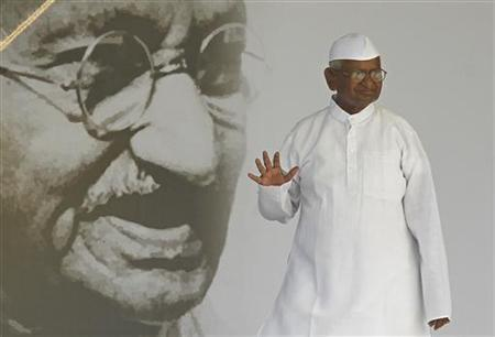 Veteran Indian social activist Anna Hazare waves to his supporters in front of a portrait of Mahatma Gandhi on the 12th day of his fasting at Ramlila grounds in New Delhi August 27, 2011. REUTERS/Adnan Abidi