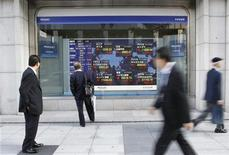 <p>Passersby look at an electronic board displaying a rise in major market indices around the world, outside a brokerage in Tokyo October 27, 2011. REUTERS/Issei Kato</p>