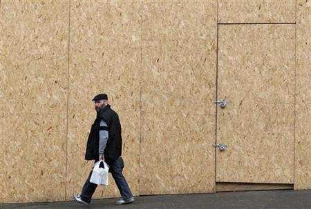 A man walks past a boarded up shop in Nottingham, central England January 25, 2011. REUTERS/Darren Staples