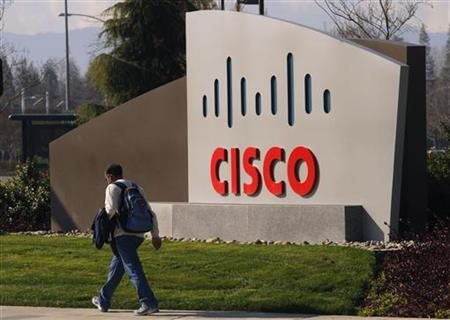 A pedestrian walks past the Cisco logo at the technology company's campus in San Jose, California February 3, 2010. REUTERS/Robert Galbraith