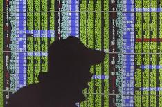 <p>A man's shadow is cast on monitors displaying stock market prices inside a brokerage in Taipei November 10, 2011. REUTERS/Pichi Chuang</p>