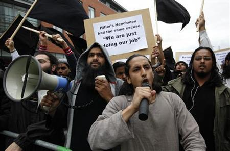 Demonstrators from a local group called ''Muslims Against Crusades'' protest during a march by the 1st Battalion, Royal Anglian Regiment, who recently returned from a combat tour in Afghanistan, through the London suburb of Barking June 15, 2010. REUTERS/Suzanne Plunkett