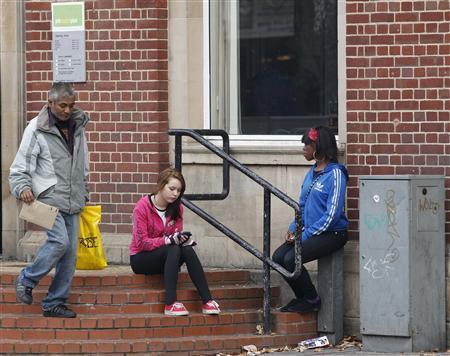 Women wait outside a Job Centre in Leicester, November 16, 2011. REUTERS/Darren Staples