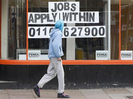 A man walks past a shop advertising job vacancies in Leicester, November 16, 2011. REUTERS/Darren Staples
