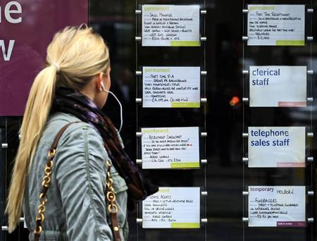 A woman passes notices for jobs in the window of a recruitment agency in London April 13, 2011. REUTERS/Luke MacGregor