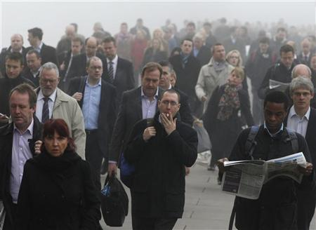 Commuters make their way in the fog across London Bridge towards the financial district of London November 23, 2011. REUTERS/Chris Helgren