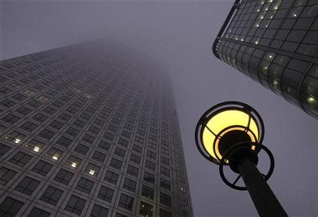 Low clouds obscure the top of One Canada Square in the Canary Wharf business district of London at dawn November 11, 2011. REUTERS/Russell Boyce