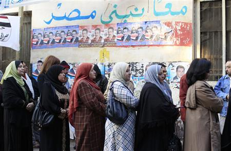 People stand in line outside a polling station as they wait to cast their votes during the parliamentary election in Cairo November 28, 2011. Polling stations opened on Monday, state television reported, in Egypt's first parliamentary election since a popular uprising ended the 30-year rule of President Hosni Mubarak in February. The writing on the wall read: ''We build Egypt together.'' REUTERS/Ahmed Jadallah