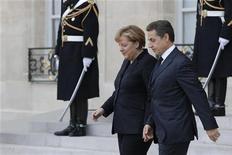 """<p>Angela Merkel et Nicolas Sarkozy lundi à l'Elysée. Pour Frank Gil, chargé des notations de la zone Europe chez S&P, l'accord conclu entre la France et l'Allemagne pour renforcer l'intégration budgétaire entre les Etats européens est """"prometteur"""" et pourrait permettre d'éviter à certains Etats de la zone euro un abaissement de leur note de crédit. /Photo prise le 5 décembre 2011/REUTERS/John Schults</p>"""
