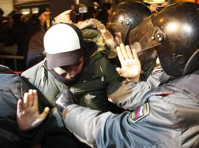 Policemen detain an activist during a rally to protest against the results of the parliamentary elections and the policies conducted by Russian authorities in Moscow December 6, 2011. REUTERS/Mikhail Voskresensky