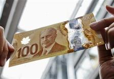 <p>A man holds the new Canadian 100 dollar bill made of polymer in Toronto November 14, 2011. REUTERS/Mark Blinch</p>