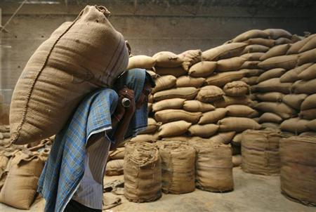 A labourer carries a sack of wheat inside a grain-sorting unit at Sanand in the western Indian state of Gujarat April 7, 2011. REUTERS/Amit Dave