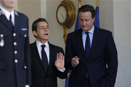 France's President Nicolas Sarkozy (L) reacts as he escorts Britain's Prime Minister David Cameron after a working lunch at the Elysee Palace in Paris December 2, 2011. REUTERS/John Schults
