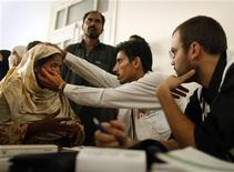 <p>Doctors from treat a woman at an emergency medical centre for flood victims operated by Medecins Sans Frontieres (MSF) in Charsadda, located in Pakistan's northwest Khyber-Pakhtunkhwa Province August 17, 2010. REUTERS/Tim Wimborne</p>
