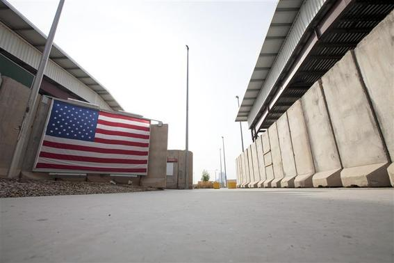 A U.S. flag hangs from blast barriers guarding the entrance to the dining facility inside the compound of the U.S. embassy in Baghdad December 14, 2011. The compound, located in Baghdad's Green Zone, will be the home for thousands of American citizens left after the U.S. military completes its withdrawal this month. REUTERS/Lucas Jackson