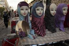 <p>A Libyan woman is reflected in a mirror as she looks at headscarves displayed on plastic models at a market stall in central Tripoli in this November 28, 2011 file photo. REUTERS/Mohammed Salem/Files</p>