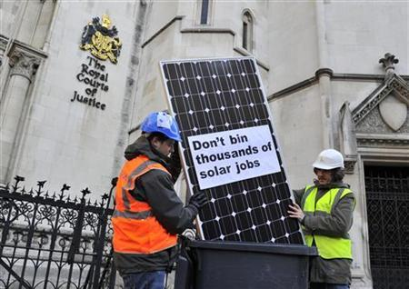 Panel installers pose with a solar panel outside the High Court in central London December 15, 2011. REUTERS/Toby Melville