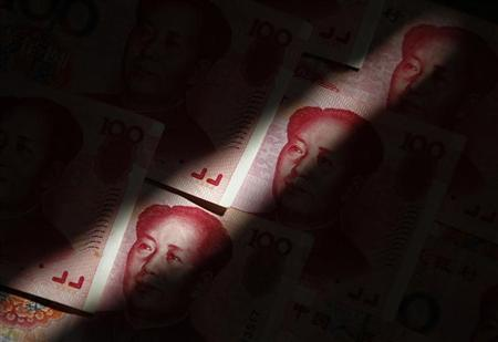 A beam of light falls on Chinese 100 yuan banknotes in this photo illustration taken in Beijing in this March 12, 2011 file photo. REUTERS/Petar Kujundzic/Files