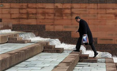 A man walks up steps in the City of London, January 25, 2010. REUTERS/Suzanne Plunkett