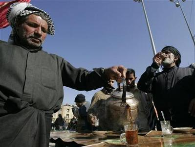 A resident presents tea to pilgrims on the road in Kerbala, 110 km (70 miles) south of Baghdad January 15, 2008. REUTERS/Ceerwan Aziz