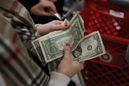 A customer counts her money while waiting in line to check out at a Target store on the shopping day dubbed ''Black Friday'' in Torrington, Connecticut November 25, 2011. REUTERS/Jessica Rinaldi