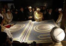 <p>Il a fallu cinq ans de labeur à un calligraphe afghan et neuf de ses élèves pour réaliser le plus grand coran du monde. Le luxueux ouvrage, exposé dans un centre culturel de Kaboul pour démontrer que le riche héritage culturel de l'Afghanistan n'a pas été détruit par trente années de conflits, compte 218 pages, mesure 2,28 m de haut pour 1,55 m de large et pèse 500 kg. /Photo prise le 12 janvier 2012/REUTERS/Mohammad Ismail</p>