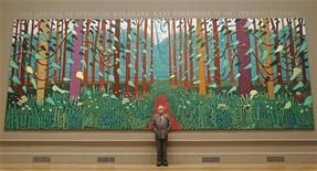 "<p>British artist David Hockney poses with his painting ""The Arrival of Spring in Woldgate, East Yorkshire in 2011 (twenty-eleven)"" at the Royal Academy of Arts in London January 16, 2012. REUTERS/Luke MacGregor</p>"