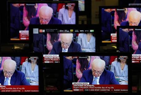 News Corp Chairman and Chief Executive Rupert Murdoch is seen on television screens in an electrical store as he is questioned by a parliamentary committee on phone hacking, in Edinburgh, Scotland July 19, 2011. REUTERS/David Moir