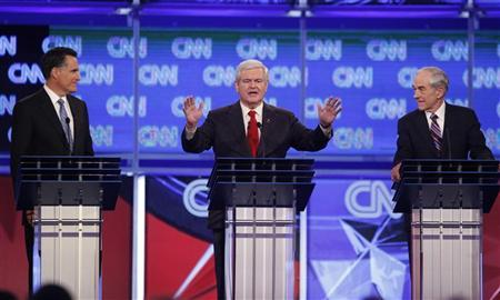 Republican presidential candidate former House Speaker Newt Gingrich (C) speaks as former Massachusetts Governor Mitt Romney (L) and U.S. Rep. Ron Paul (R-TX) look on during the Republican presidential candidates debate in Charleston, South Carolina, January 19, 2012. REUTERS/Jason Reed