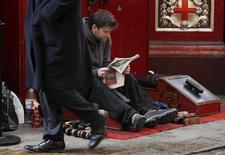 <p>A pedestrian passes a man sat waiting at a shoe shine stall in the City of London January 20, 2012. REUTERS/Luke MacGregor</p>